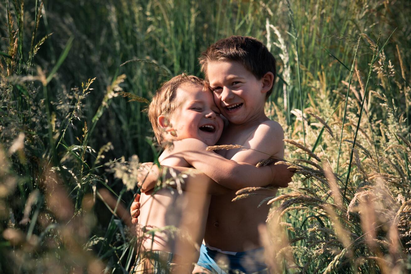 Twee kindjes aan het knuffelen in het gras
